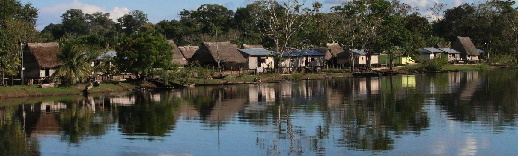 Sarah Papworth's peruvian amazon photo,  river and houses along the bank. reflection of blue sky and clouds in the river